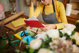 Portrait of small business owner holding red envelope while doing accounting in flower shop, copy space - 245893207