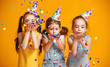 Leinwandbild Motiv happy birthday children girls with confetti on yellow background