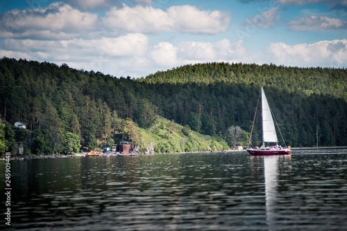 yacht, pleasure boat, sailboat against the blue sky and mountains, lake turgoyak