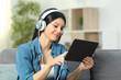 Leinwandbild Motiv Happy woman browsing and listening videos on tablet