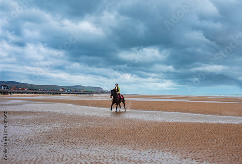 Jolie cavalière sur la plage en automne