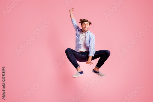 Leinwandbild Motiv Full length body size photo of jumping high crazy he his him handsome unusual pose shape figure dancing glad wearing casual jeans checkered plaid shirt isolated on rose background