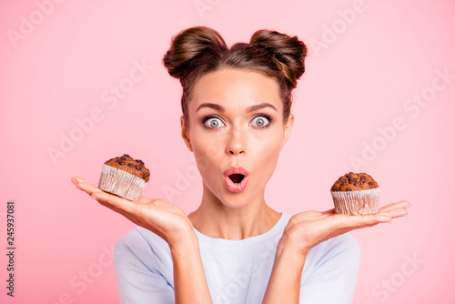 Leinwandbild Motiv Close-up portrait of nice lovely cute attractive amazed scared afraid girl holding in hands two cakes choosing deciding dilemma opened mouth isolated over pink pastel background