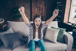 Leinwanddruck Bild - Ecstatic sweet beautiful glad positive charming with opened mouth styles stylish staring eyes she her lady sitting on couch raising fists up