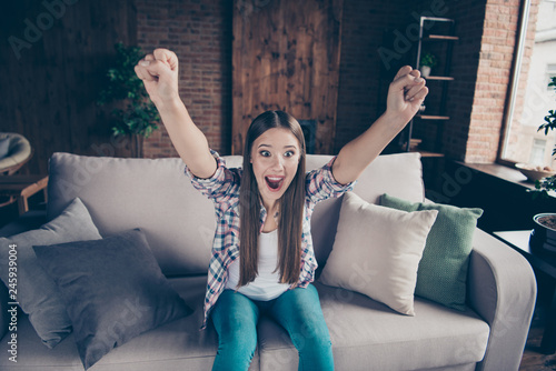 Leinwanddruck Bild Ecstatic sweet beautiful glad positive charming with opened mouth styles stylish staring eyes she her lady sitting on couch raising fists up