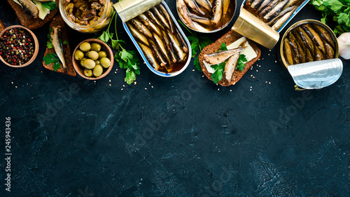 Foto Murales Assortment of sprats in oil. Smoked fish On a black background. top view. Free copy space.
