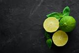 Fresh green limes. Lemon. On a black background. Top view. Free copy space.