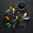 Black pasta with mussels on a black stone background. Top view. Free space for your text.