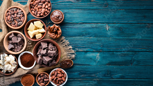 fototapeta na ścianę Chocolate, cocoa and cocoa beans on a blue wooden background. Top view. Free copy space.