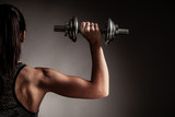 young athlet workout in fitness gym - train with dumbbell