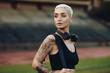 Leinwandbild Motiv Portrait of a woman runner standing in an athletic stadium
