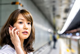 Japanese woman using a smartphone waiting for the arrival of the subway - 245961214