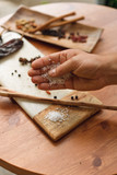 Male hand of a chef pouring out salt on a wooden desk with different spices and ingridients, ready foor cooking - 245976856