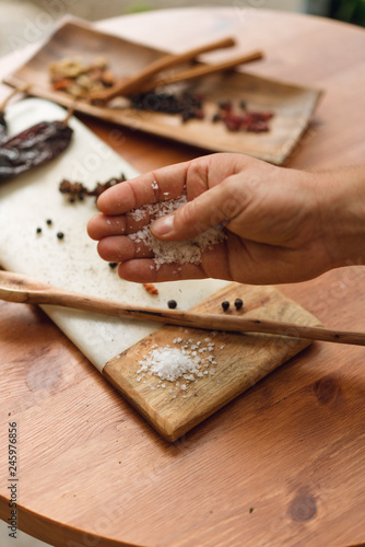 Male hand of a chef pouring out salt on a wooden desk with different spices and ingridients, ready foor cooking