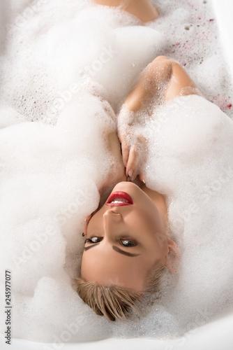 Leinwanddruck Bild Erotic young blonde in foam bath