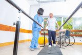 Asian nurse helping elderly man in the 70s making physiotherapy on treadmill - 245977216