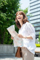 Tokyo. Japanese tourist woman in 30s with the map visiting the city. Travel concept