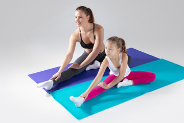 Beautiful woman and her little daughter are doing exercises on mats © alexsokolov