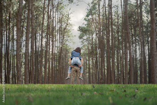 Girl riding behind a young man in a pine forest