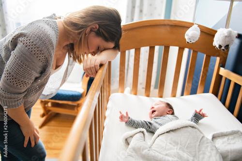 Leinwandbild Motiv Tired Mother with Upset Baby Suffering with Post Natal Depression.