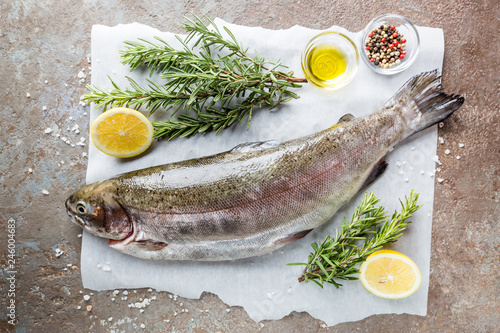 Leinwanddruck Bild Raw trout fish on paper with rosemary and lemon on a stone table, top view