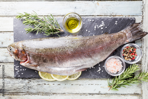 Leinwandbild Motiv Raw trout fish on slate with rosemary and lemon over white wooden table, top view