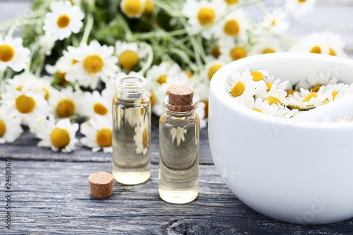 Bottle of chamomile oil with mortar and flowers on wooden table - 246013673