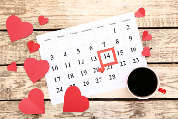 Valentine day calendar with paper hearts and cup of coffee on wooden table