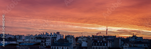 Sunrise over Paris roofs in winter with clouds and smoking chimneys - France - 246024245