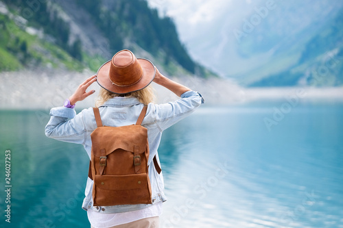 Traveler-Image. Traveler look at the mountain lake. Travel and active life concept. Adventure and travel in the mountains region in the Austria. - 246027253