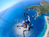 Paragliding in the sky. Paraglider tandem flying over the sea with blue water and mountains in bright sunny day. Aerial view of paraglider and Blue Lagoon in Oludeniz, Turkey. Extreme sport. Landscape - 246035070