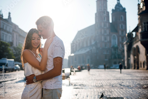 Happy young couple in love hugging while standing on the square in Krakow, Poland on sunny summer day