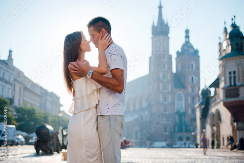Romantic young couple in love hugging and kissing while standing on the square in Krakow, Poland on sunny summer day