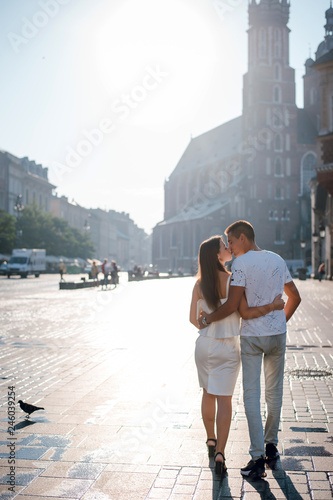 Rear view of young couple in love kissing while walking on the square in Krakow, Poland. Beautiful sunny day