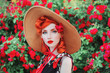 Girl with red lips in rose print dress on summer garden. Spring blossom flower. Redhead model in summer hat on valentines background of blossom rose bush. Stylish woman. Spring flower garden