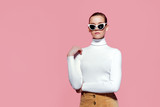 Fashion studio image of gorgeous elegant woman in white knitted golf and sunglasses posing over pink wall. - 246045899