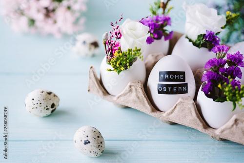 Leinwandbild Motiv Ostergrußkarte / Osterdekoration mit Ostereiern und kleinen Blumen mit blauem Hintergrund