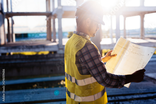 Foto Murales Picture of construction site engineer looking at plan