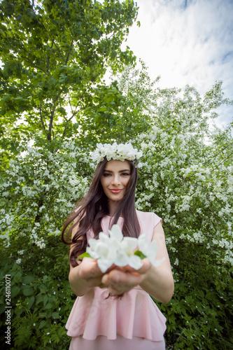 Leinwandbild Motiv Attractive young woman in flowers wreath  in spring blossom garden outdoors. Beautiful girl outdoor portrait