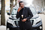 Stylish african american gentleman in elegant black jacket, holding retro walking stick as cane flask or tippling cane. Rich fashionable afro man against business suv car speaking on mobile phone.