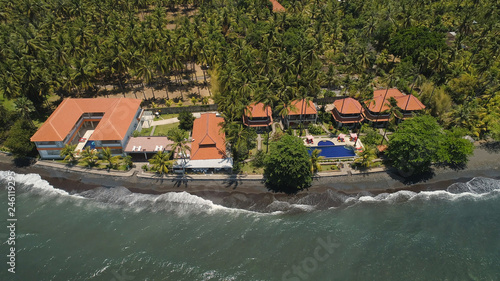aerial view luxury hotel with swimming pool, sun beds, palm trees by sea. seascape coastline with black sand beach, palm trees, hotel, tropical resort. Bali,Indonesia, travel concept. - 246119295