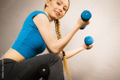 Teenage woman working out at home with dumbbell - 246124865