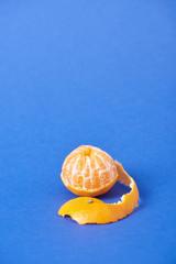peeled juicy tangerine with zest on blue background