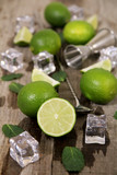 Lime, mint, ice with bar utensils on wooden table. Ingredients for Mojito cocktail making.