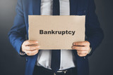 bankruptcy  text on paper on business man hand - 246143476