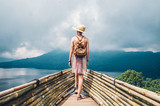 Fototapeta Natura - Traveller woman with a backpack looking at the amazing landscape travelling the world  © Kar Tr