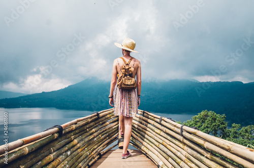 Traveller woman with a backpack looking at the amazing landscape travelling the world