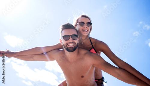 Leinwandbild Motiv Man carrying woman piggyback on beach.
