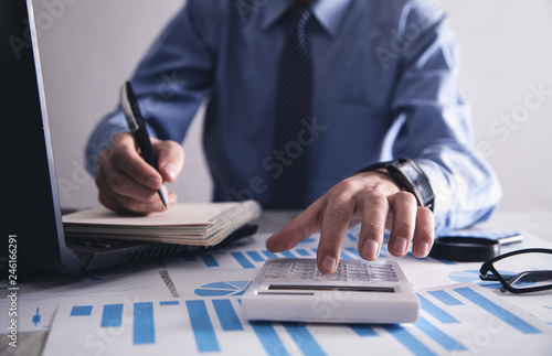 Businessman working in office and using calculator. © andranik123