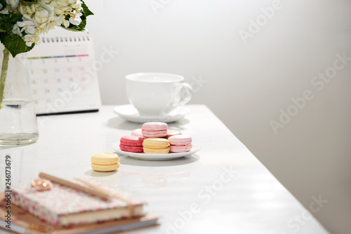 Office table desk. Feminine desk workspace frame with calendar, diary, hortensia bouquet, macaron and coffee on white background. ideas, notes or plan writing concept - 246173679